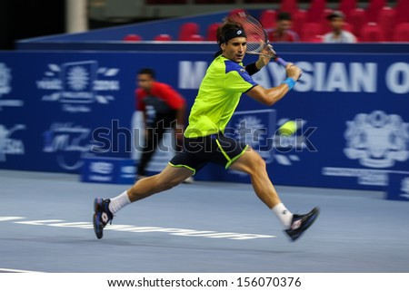 KUALA LUMPUR - SEPTEMBER 27: David Ferrer chases to hit a return to Joao Sousa in a quarter-final match of the Malaysia Open 2013 tennis played at the Putra Stadium, Malaysia on September 27, 2013. - stock photo