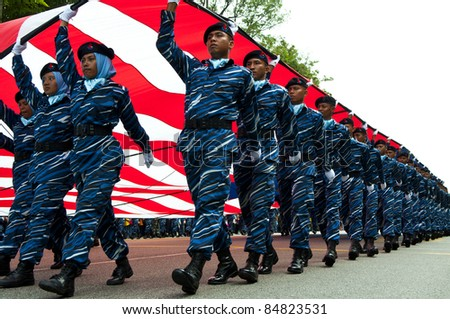 KUANTAN - SEPT 16: PLKN trainee carry flag in the National Day and Malaysia Day parade, celebrating the 54th anniversary of independence on September 16, 2011 in Kuantan, Pahang, Malaysia.