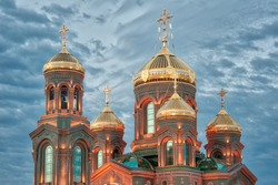 KUBINKA, MOSCOW REGION, RUSSIA - Shining gold domes (cupolas) of the Resurrection Cathedral, the Main Church of Russian Armed Forces in Kubinka, illuminated in the twilight on the last day of summer.