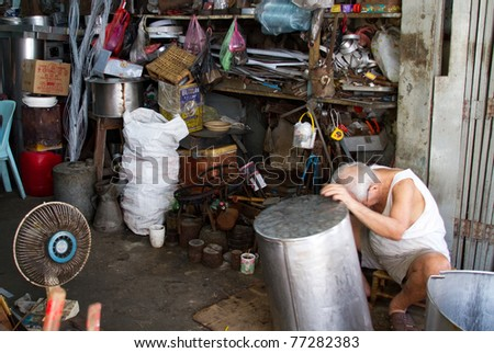 KUCHING, BORNEO ISLAND - MAY 13: An unidentified traditional craftsman makes aluminum products the old way in their shop on the streets of Kuching, May 13, 2010 in Kuching, Borneo Island. Most of these goods are produced by modern factories today.