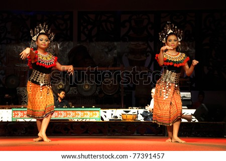 KUCHING, MALAYSIA - MAY 14: Young girls from the indigenous Iban people perform a traditional dance at the Sarawak Cultural Village, May14, 2010 in Kuching. The Ibans were known to be head-hunters in the past.