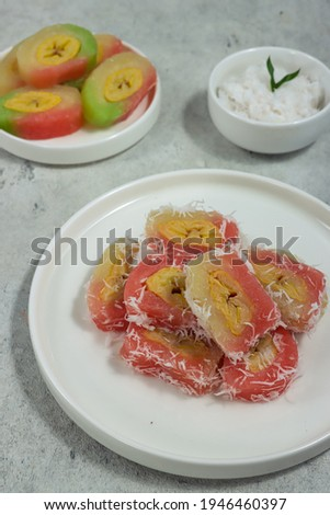 Kue mata roda or grubi is Indonesian traditional cake made from cassava, the center of which is filled with bananas, shaped like a wheel, served with grated coconut. Zdjęcia stock ©