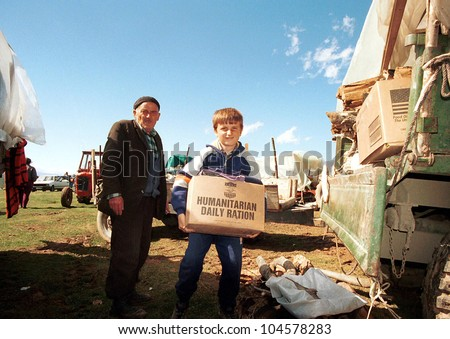 KUKES, ALBANIA, 17 APRIL 1999 --- A young  Kosovar Albanian refugee  returns to his camp in northern Albania with an aid packages distributed by the United States government.