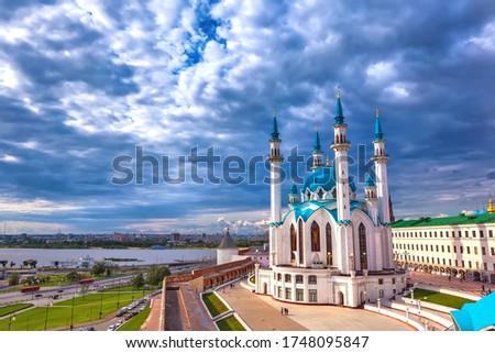 Kul Sharif Mosque in the Kazan Kremlin, Tatarstan, Russia - Jule 2015. A majestic white stone mosque with a blue roof surrounded by a red brick wall in cloudy weather with heavy rain clouds.