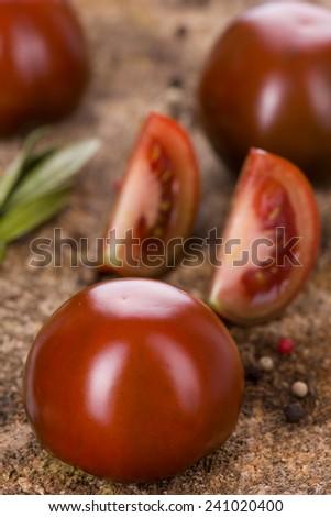 Kumato, black tomatoes on wooden background
