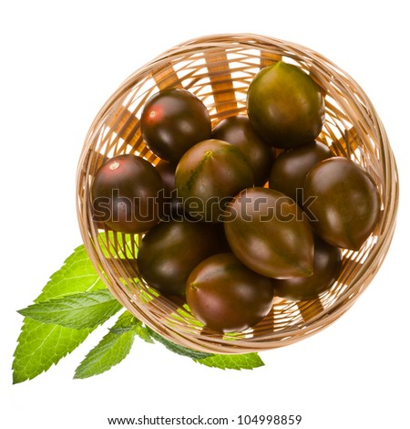 kumato green  cherry tomatoes in a wicker basket with green leaves isolated on white background