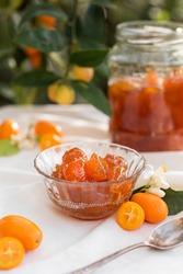 Kumquat jam with fresh kumquats with jar and garden on the background