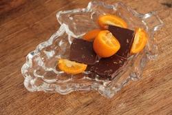 Kumquats and chocolates in glass plate. Half and slice kumquat fruits. Fresh Cumquat and piece of chocolate.