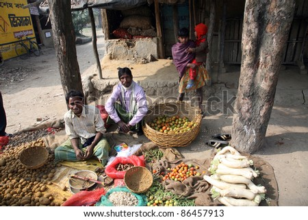 KUMROKHALI, INDIA - JANUARY 14: Tribal villagers bargain for vegetables on January 14, 2009. Kumrokhali, West Bengal, India. 42% of India falls below the international poverty line of $1.25 a day