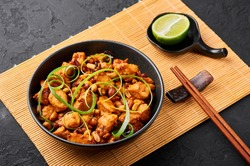 Kung Pao Chicken or Gong Bao Ji Ding at dark slate background. Sichuan Kung Pao is chinese cuisine dish with chicken meat, chilli peppers, peanuts, sauces and onion.