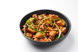 Kung Pao Chicken or Gong Bao Ji Ding isolated on white background. Sichuan Kung Pao is chinese cuisine dish with chicken meat, chilli peppers, peanuts, sauces and onion.