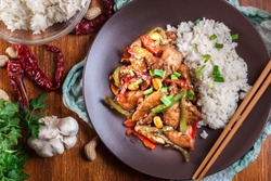 Kung Pao chicken with peppers and vegetables served with rice. Traditional sichuan dish. Top view