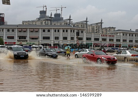 KUNMING - JULY 19: Unidentified people and vehicles caught in the flooded streets after intense rain storms, Kunming China July 19, 2013 - stock photo