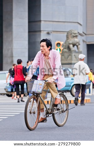 KUNMING-JUNE 30, 2014. Middle aged man cycles in city center. With a population of 1,342,700,000, 500,000,000 bicycles and 37.2 cyclists China is still the number one bicycle country in the world.