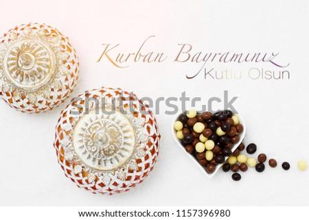 Kurban Bayramı sacrifice festival, Islamic Arabic candle and chocolate sugar. Kurban bayraminiz kutlu olsun means happy festival of sacrifices #1157396980