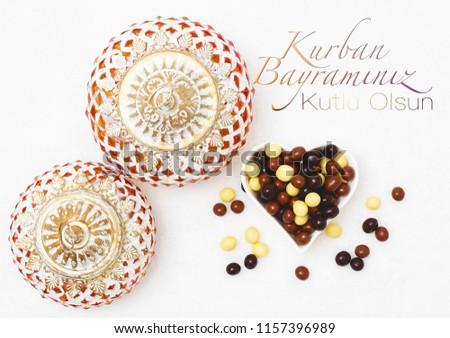 Kurban Bayramı sacrifice festival, Islamic Arabic candle and chocolate sugar. Kurban bayraminiz kutlu olsun means happy festival of sacrifices #1157396989