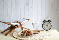 Kurma or dates fruit with glass of mineral water, holy book Al-Quran, alarm clock and prayer beads on the table. Traditional Ramadan, iftar meal. Ramadan kareem fasting month concept