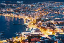 Kusadasi, Aydin Province, Turkey. Waterfront And Kusadasi Cityscape In Summer Evening. Night Scenic View Of Kusadasi Skyline At Aegean Coast, Turkey.
