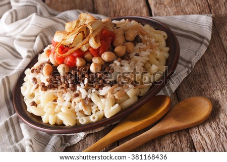 kushari of rice, pasta, chickpeas and lentils close up on a plate on the table. Horizontal