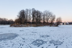 Kuskovsky island  in Kuskovo park in winter at sunset.  Winter ice fishing holes in the ice of Frozen Large Palace pond. Moscow, Russia, 2020.