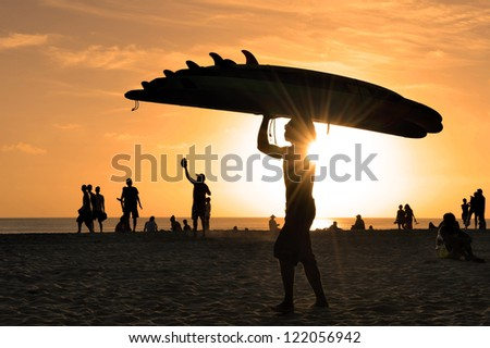 Kuta beach in Bali at sunset with man carrying surfboards