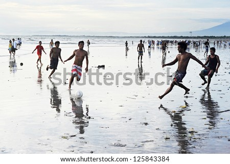 KUTA, INDONESIA - APRIL 4: Unidetified people plaing soccer on  April 4, 2011 in Kuta, Indonesia. Football is the most popular sport in Indonesia. The Indonesian football league started around 1930