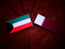 Kuwaiti flag with Qatari flag on a tree stump isolated