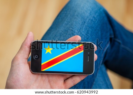 Kyiv - February11: Male hand holding iPhone with Democratic Republic of the Congo flag on the display. Ukraine, February11,2017. In processing image applied only cropping and color adjustments #620943992