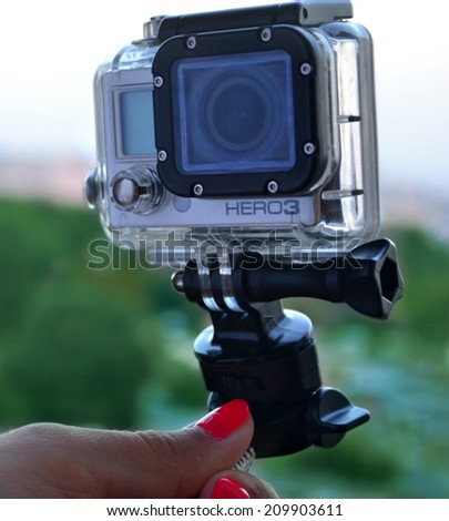 KYIV, UKRAINE - AUGUST 6, 2014: Hand holding small GoPro hero3 camera often used in extreme action video photography.