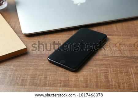 KYIV, UKRAINE - DECEMBER 18, 2017: Modern iPhone 8 Space Gray on wooden table
