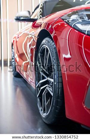 Kyiv,Ukraine - FEBRUARY 4, 2019: metal car wheel and tire of red metallic BMW Z4 sport car,selective focus, at Ukrainian Fashion Week FW19-20 on February 4,2019 in Ukraine,Kyiv. #1330854752