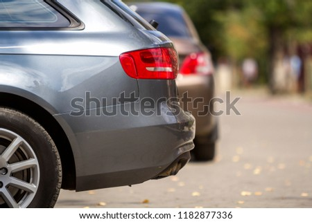 KYIV, UKRAINE - July 9, 2018: Vehicles design concept Close up side view details of new shiny luxurious silver car parked in recreation park district on blurred bright green trees bokeh background. #1182877336