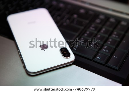KYIV,UKRAINE-4 NOVEMBER,2017:New Iphone X in white color.Latest Apple Iphone 10 smartphone model on notebook keyboard.Modern mobile phone with vertical dual camera on back