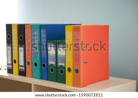 Kyiv, Ukraine - October 2, 2019: Stack of colorful binders with office documents on a working table.