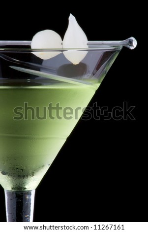 Kyoto cocktail in chilled martini glass over black background on reflection surface. Green color, gin, dry vermouth, melon liqueur,  garnished with marinated pearl onions.