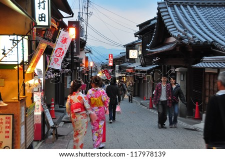 KYOTO, JAPAN - APRIL 9 2012: Tourists walk on a street leading to Kiyomizu Temple on April 9 2012 for Sakura viewing. Kiyomizu is a famous temple in Kyoto built in year 778.