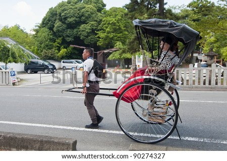 KYOTO, JAPAN-JULY 15:jinrikisha driven by an unidentified driver carrying two Japanese tourists on July 15,2011 in Kyoto,Japan.The word jinrikisha is of Japanese origin and means human-powered vehicle
