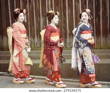 KYOTO March 18 2013 Three beautiful Japanese girls walking down a street in the Gion district of Kyoto Japan a very old traditional city