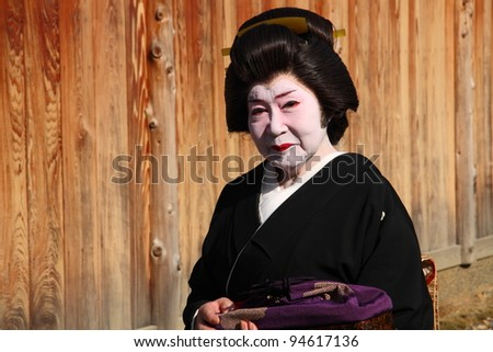 KYOTO - NOV 21: Unidentified old geisha outdoors on November 21 2009 in Gion district, Kyoto, Japan. Geishas are skilled in traditional arts such as music, dance, singing and tea ceremony.