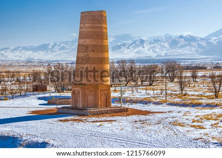 Kyrgyzstan - Tokmak - Impressive falling Burana tower, UNESCO world heritage site located on ancient great silk road with blured maountain landscape behind Stok fotoğraf ©