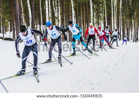 Kyshtym, Russia -  March 26, 2016: group of skiers athletes men in forest free style uphill during Championship on cross country skiing #550449835