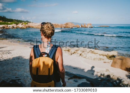 La Digue Island, Seychelles. Adult women with backpack enjoying beautiful tropical secluded beach in evening light Photo stock ©