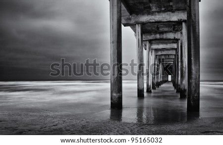 La Jolla beach, California,  long exposure under the pylons, black and white image.