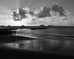 La Laja beach at sunrise, ships and sky with low clouds, Las Palmas of Gran Canaria, Spain