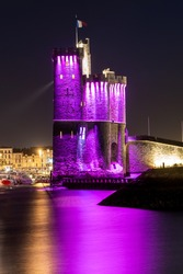 La Rochelle old harbor with its famous Saint-Nicolas tower. Night shot with pink lights for pink october. Pink October is breast cancer awareness month