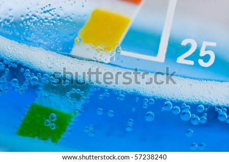 Lab chemistry - bubbles reaction in flasks with PH indicator - stock photo