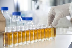 Lab / Laboratory closeup of hand in sterile gloves straighten out a glass bottle filled with liquid. E-Liquid, Chemical Filling, Manufacturing, Science, Scientist, Medicine, Chemistry, Pharmaceutical