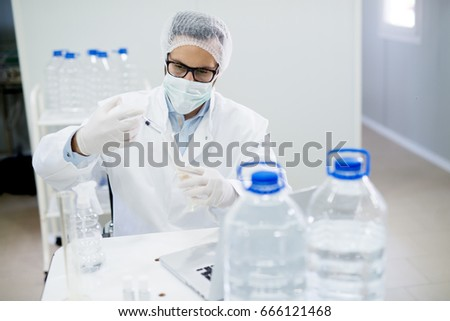 Lab technician doing chemical analysis. Testing chemical composition of the water.