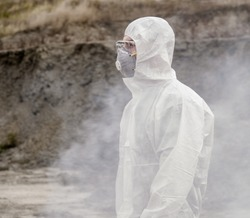 Lab technician in a mask and chemical protective suit, walks on dry ground with a tool box through toxic smoke.