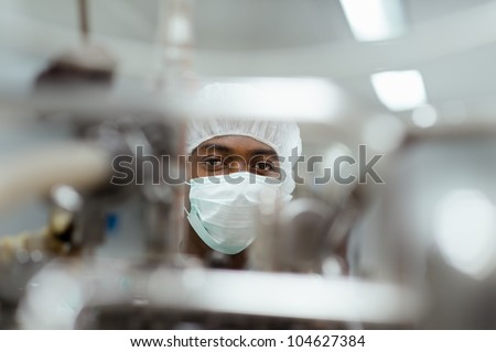 Lab technician working as researcher in biotechnology plant with machinery